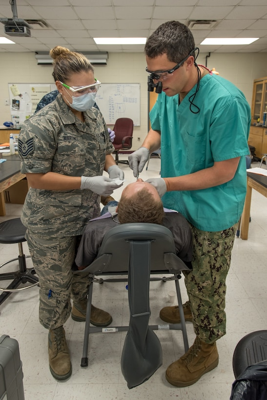 U.S. Air Force Tech. Sgt. Jessica Martinez (left), a dental technician from the Iowa Air National Guard's 185th Refueling Wing, and U.S. Navy Lt. Cmdr. Jay Ross, a dentist from Expeditionary Medical Facility Camp Pendleton in California, perform a dental procedure at a health-care clinic at Owsley County High School in Booneville, Ky., June 24, 2018. The clinic is one of four that comprised Operation Bobcat, a 10-day mission to provide military medical troops with crucial training in field operations and logistics while offering no-cost health care to the residents of Eastern Kentucky. The clinics, which operated from June 15-24, offered non-emergent medical care; sports physicals; dental cleanings, fillings and extractions; eye exams and no-cost prescription eye glasses. (U.S. Air National Guard photo by Lt. Col. Dale Greer)