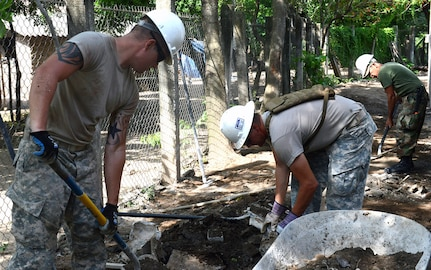 Soldiers from the 4th Engineer Battalion, Fort Carson, Colorado, remove rubble to make way for a sidewalk to a school they are building in rural El Salvador June 23.