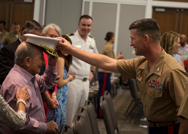Colonel Jeffrey C. Smitherman, Commanding Officer of 6th Marine Corps District, hands his cover to an attendant of the Recruiting Station Jacksonville change of command ceremony in Jacksonville, Florida, June 22, 2018. During the ceremony, Maj. Michael Valenti, the outgoing commanding officer for RS Jacksonville, will relinquish his command to Maj. Joseph Gill.