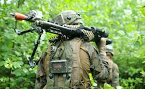 A U.S. Marine from 1st Battalion, 6th Marines maneuvers through a forest during Exercise Saber Strike 18, near Skrunda, Latvia, June 11, 2018. Marines with Black Sea Rotational Force participated in Exercise Saber Strike, which is an integrated field-training exercise that occurs annually throughout Estonia, Latvia, Lithuania and Poland, increasing joint operational capability and enhancing the NATO alliance.