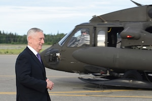 Defense Secretary James N. Mattis walks by a UH-60 Black Hawk helicopter