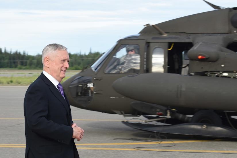 Defense Secretary James N. Mattis walks by a UH-60 Black Hawk helicopter