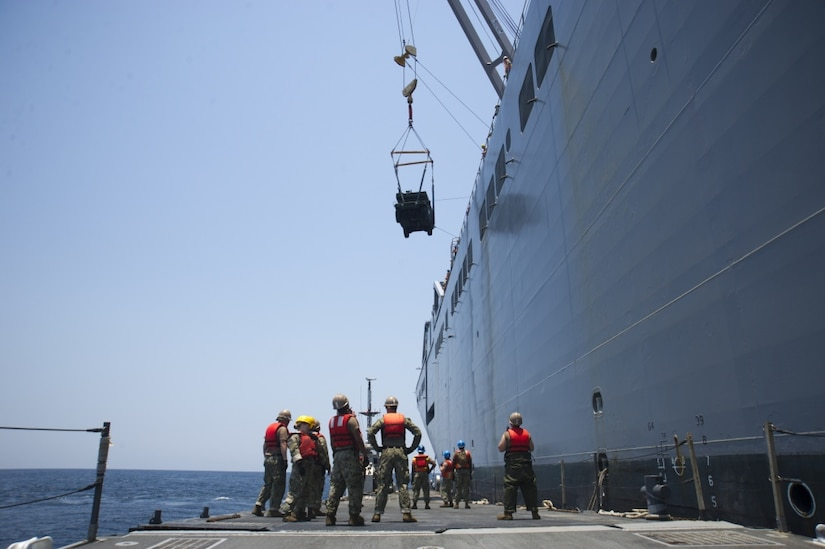 Sailors and soldiers lower an ambulance to a ferry's flight deck using cranes.
