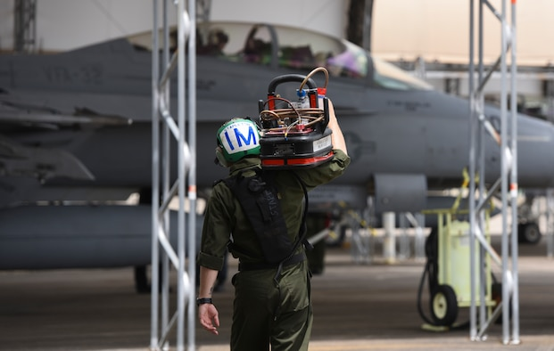 A sailor from the Naval Air Station Oceana carries hydraulic fluid to an F/A-18 assigned to Strike Fighter Squadron (VFA) 32 during training June 18, 2018, at Eglin Air Force Base, Fla. The purpose of this training is to familiarize Navy pilots and maintainers with the F-35 Lightning II.  (U.S. Air Force photo by Airman 1st Class Daniella Peña-Pavao)