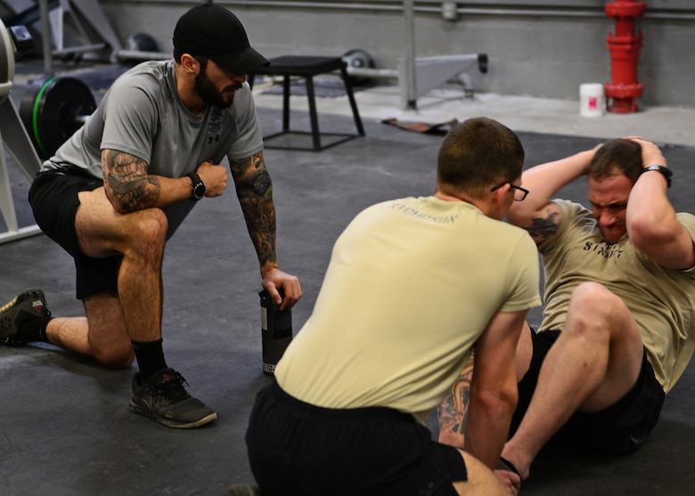 Adam DeRycke, a Survival, Evasion, Resistance and Escape Specialist Training Orientation Course instructor and training manager, at left, monitors the performance of candidates during a mock physical fitness assessment at the SERE specialist schoolhouse at Joint Base San Antonio-Lackland, Texas, March 22, 2018. Candidates are critiqued on physical training, backpacking, basic public speaking, outdoor living and survival skills and improvising to assess their potential success as a future SERE specialist. (U.S. Air Force photo by Staff Sgt. Chip Pons)