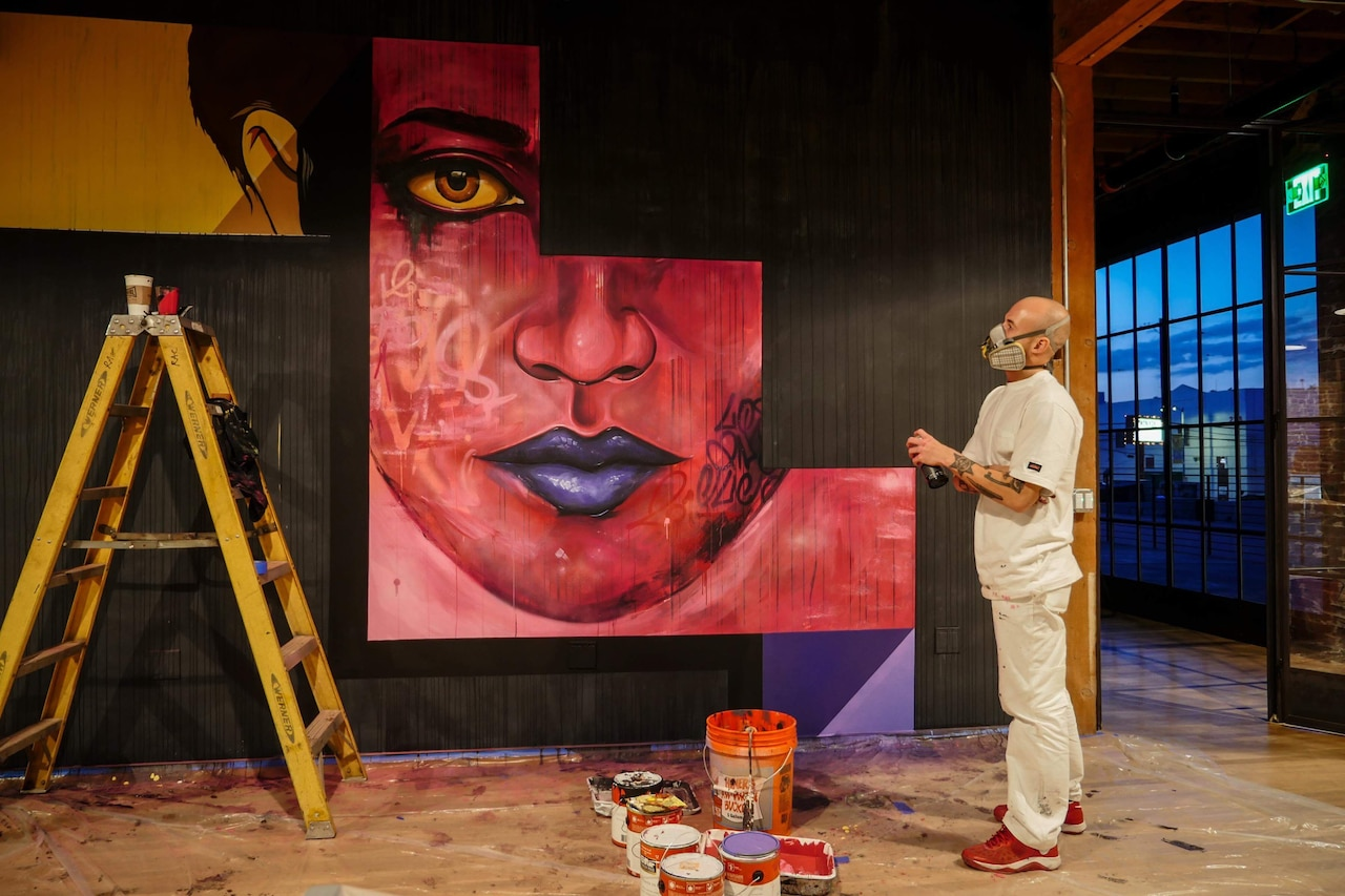 Airman paints a large mural of a face.
