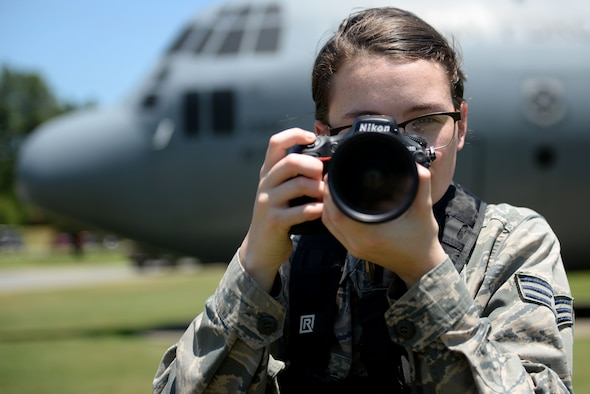 A woman in uniform stands outside with a camera to her eye.