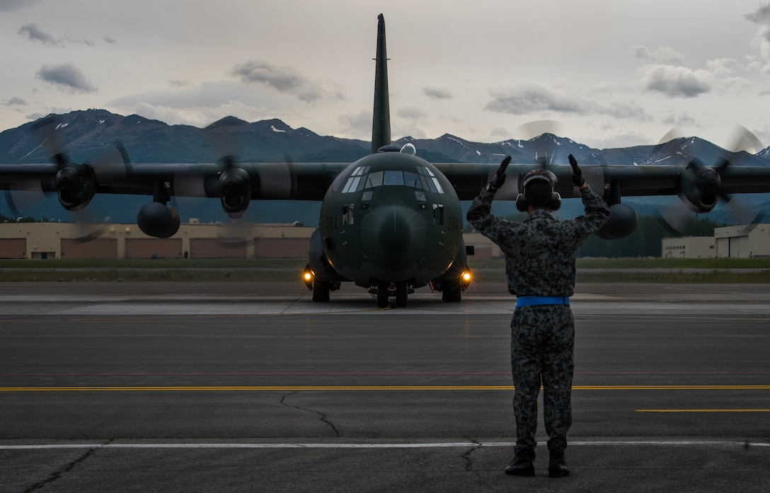 A Japan Air Self-Defense Force Airman marshals a JASDF C-130H Hercules aircraft from Hamamatsu Air Base, Japan, prior to takeoff during Red Flag-Alaska 18-2 operations at Joint Base Elmendorf-Richardson, Alaska, June 21, 2018. Seventy-seven JASDF Airmen operated out of JBER for Pacific Air Forces' premier air combat exercise. Since its inception, thousands of service members from all branches of the U.S. military, as well as armed services of multiple countries from around the world, have taken part in Red Flag-Alaska.
