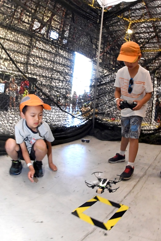 James Che (left) watches his friend Ethan Tang fly a drone during the Warriors Over the Wasatch Air and Space Show June 24, 2018, at Hill Air Force Base, Utah. The drone play area was one of numerous exhibits and activities associated with STEM City at the Hill Air Show June 23-24, an area dedicated to encouraging students and educating parents about opportunities in science, technology, engineering and math.(U.S. Air Force Photo by Todd Cromar)