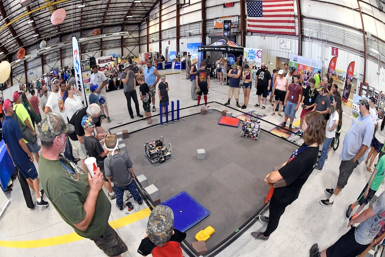 "Air show visitors operate and perform tasks with robots at the ""First Tech Challenge"" display during the Warriors Over the Wasatch Air and Space Show June 24, 2018, at Hill Air Force Base, Utah. The display was one of  numerous exhibits and activities associated with STEM City at the Hill Air Show June 23-24, an area dedicated to encouraging students and educating parents about opportunities in science, technology, engineering and math.(U.S. Air Force Photo by Todd Cromar)"