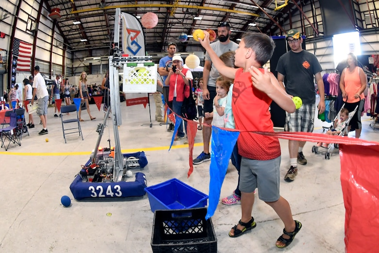 "Dakota Baker throws a ball into a basket attached to a moving robot at the ""First Is"" display during the Warriors Over the Wasatch Air and Space Show June 24, 2018, at Hill Air Force Base, Utah. The diplay was one of numerous exhibits and activities associated with STEM City at the Hill Air Show June 23-24, an area dedicated to encouraging students and educating parents about opportunities in science, technology, engineering and math.(U.S. Air Force Photo by Todd Cromar)"