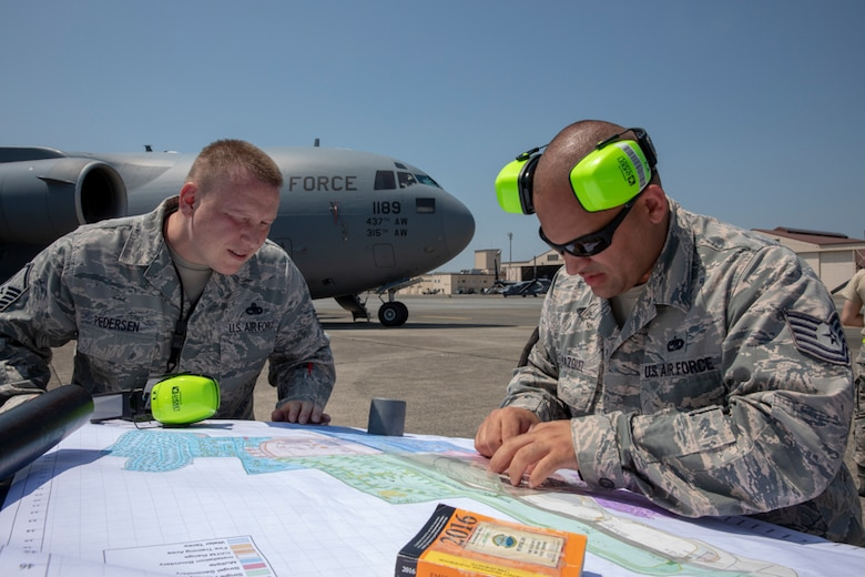 Tech. Sgt. Brandon Vasquez and Master Sgt. Lee Pedersen, both 730th Air Mobility Squadron crew chief, plot out the cordon during an Emergency Response Exercise