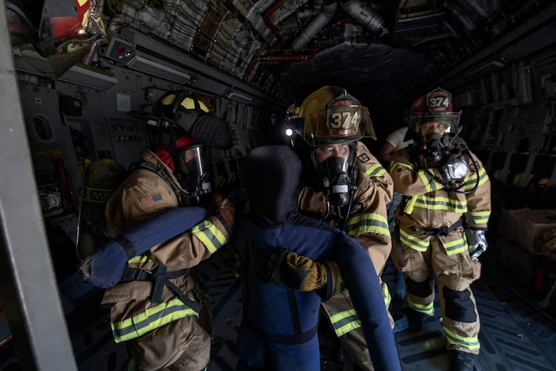 Firefighters from the 374th Civil Engineer Squadron pull a simulated patient from a C-17 Globemaster III cockpit during an Emergency Response Exercise