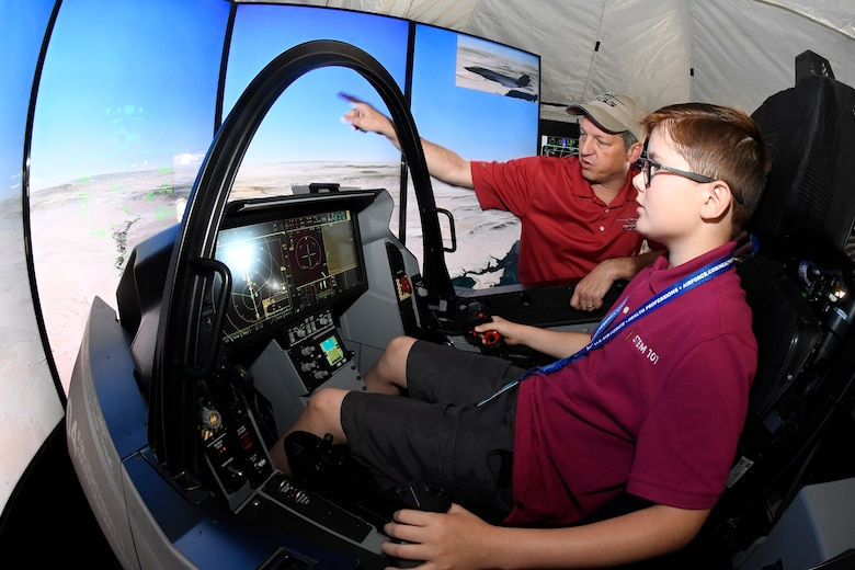 Mark Bosley, Lockheed Martin representative, instructs Cole Nickelson, in an F-35 flight simulator during the Warriors Over the Wasatch Air and Space Show June 24, 2018, at Hill Air Force Base, Utah. The simulator was one of  numerous exhibits and activities associated with STEM City at the Hill Air Show June 23-24, an area dedicated to encouraging students and educating parents about opportunities in science, technology, engineering and math.(U.S. Air Force Photo by Todd Cromar)