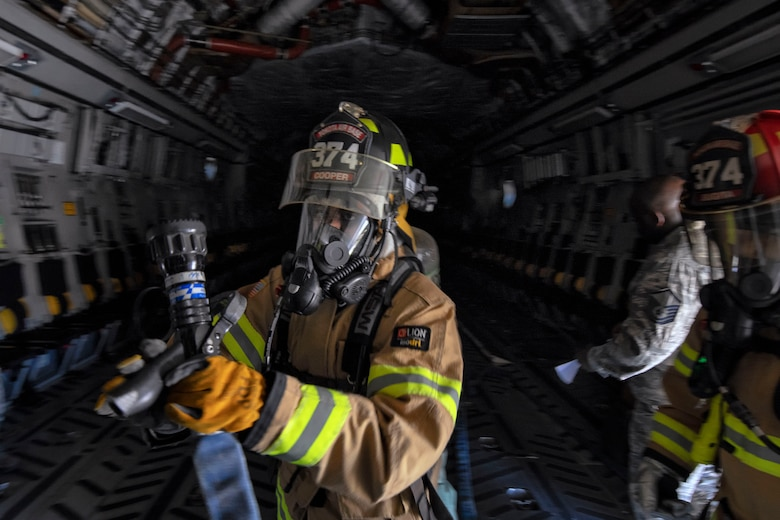 Senior Airman Tianna Cooper, 374th Civil Engieer Squadron firefighter, conducts initial entry of a simulated sire aboard a C-17 Globemaster III