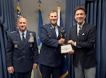 Lt. Col Daniel Finnegan receives the Koren Kolligian Trophy from Mr. Koren Kollegin II, Koren Jr.'s Nephew and Air Force Chief of Staff Gen. David L. Goldfein during a ceremony in the Pentagon,  Arlington, Va., June 25, 2018. (U.S. Air Force photo by Wayne A. Clark)