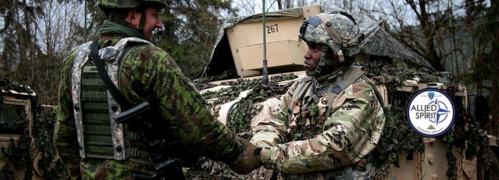 Sgt Azeez Bilaali (right), a psychological operations specialist assigned to 351st Tactical Psychological Operations Company in Fort Totten, N.Y., shakes hands with Sgt. Rimas Rimkus, a soldier in the Lithuanian armed forces, after a mission brief during the Allied Spirit VII training evercise in Grafenwoehr, Germany on Nov. 17, 2017.