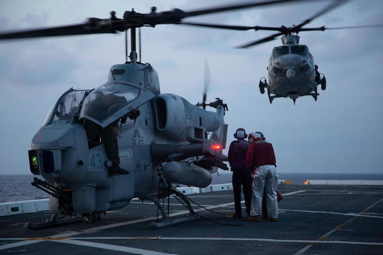 "U.S. Navy flight crew with USS Arlington refuel a AH-1W ""Super Cobra"" attack helicopter with the 22nd Marine Expeditionary Unit as UH-1Y Huey ""Venom"" utility helicopter approaches the flight deck during Amphibious Squadron MEU Integration training in the Atlantic Ocean, June 13, 2018. PHIBRON-MEU Integration is a two-week training evolution that allows Sailors and Marines to train as a cohesive unit in preparation for their upcoming deployment."