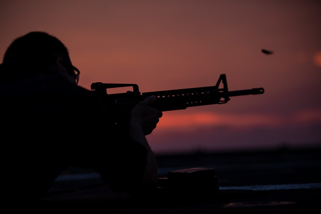 A U.S. Sailor fires an M4 carbine as part of a small arms qualification course on the USS Fort McHenry flight deck during the Amphibious Squadron MEU Integration training in the Atlantic Ocean, June 17, 2018. Enhancing the integration of the Navy-Marine Corps team, PHIBRON-MEU is a two-week training evolution that allows U.S. Sailors and Marines to combine individual and unit skills in preparation for their upcoming deployment.
