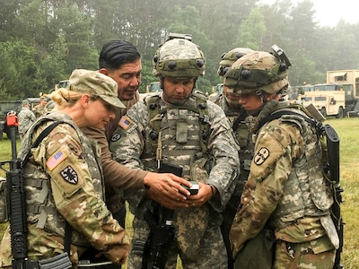Soldiers use a device to check for electromagnetic interference.