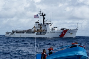 A Coast Guard cutter floats in the ocean as its crew performs a drug interdiction operation.