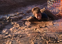A participant crawls through an obstacle at the 56th Force Support Squadron's 2018 Jump in the Mud 5K June 22, 2018 at Luke Air Force Base, Ariz.