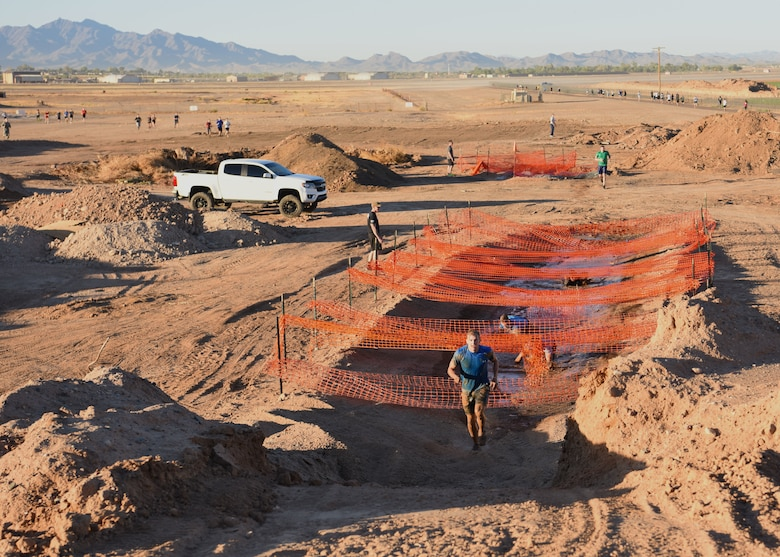 Airmen run through the first two obstacles of the 56th Force Support Squadron's 2018 Jump in the Mud 5K June 22, 2018, at Luke Air Force Base, Ariz