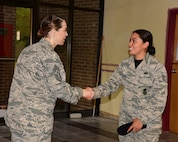 U.S. Air Force Chief Master Sgt. Juliet Gudgel, command chief of Air Education and Training Command, coins Staff Sgt. Mariel Constantino Rodriguez, 14th Security Forces Squadron noncommissioned officer in charge of standards and evaluation, at Columbus Air Force Base, Mississippi, June 22, 2018. Gudgel coined many top performing Team BLAZE Airmen for their hard work and dedication. (U.S. Air Force photo by Elizabeth Owens)