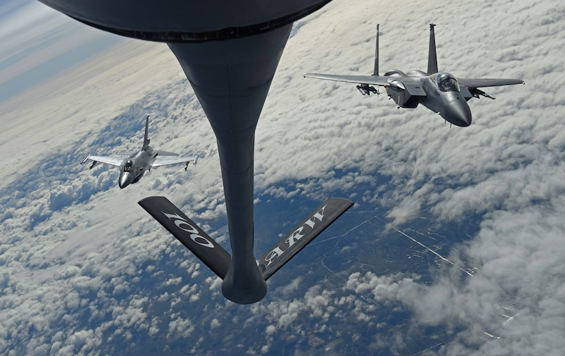 Fighter jets fly behind aerial refueling tanker.