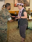 Lyndsay Kaulave, deputy command inspector, is congratulated by Col. Sakou Karega, base commander, after presenting her with a Civilian Meritorious Service Award in recognition of her outstanding work during her tenure aboard Marine Corps Logistics Barstow, June 26.