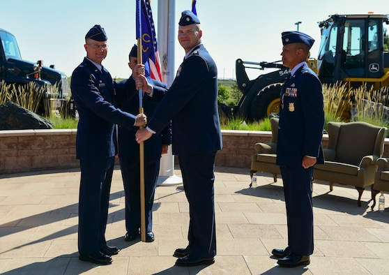 Lt. Col. Christopher Eyle, incoming 460th Civil Engineer Squadron commander, center, receives the guidon from Col. Shawn Thompson, 460th Mission Support Group commander, left, June 27th, 2018 on Buckley Air Force Base, Colorado. The exchanging of the guidon symbolizes the official change of command. (U.S. Air Force photo by Airman 1st Class Jake Deatherage)