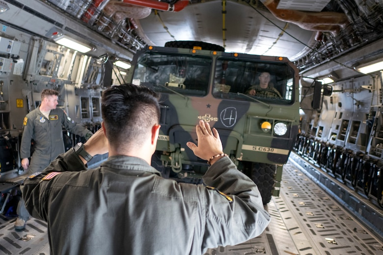 Staff Sgt. Josh Moracco, 204th Airlift Squadron loadmaster guides a heavy expanded mobility tactical truck onto a C-17 Globemaster III, operated by the Hawaii Air National Guard, during exercise Swift Response 18 on June 9, 2018, at Ramstein Air Base, Germany