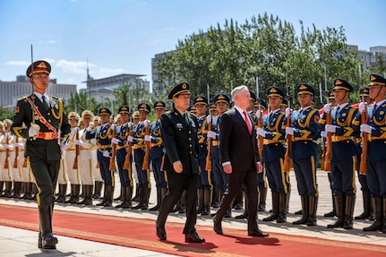 Defense Secretary James N. Mattis and his Chinese counterpart walk on a red carpet past a line of troops outside.