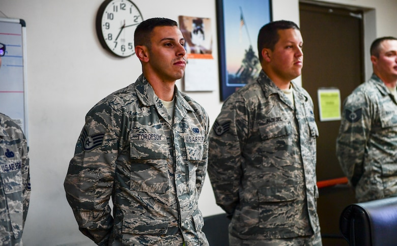 Airmen standing together during a practice board presentation.