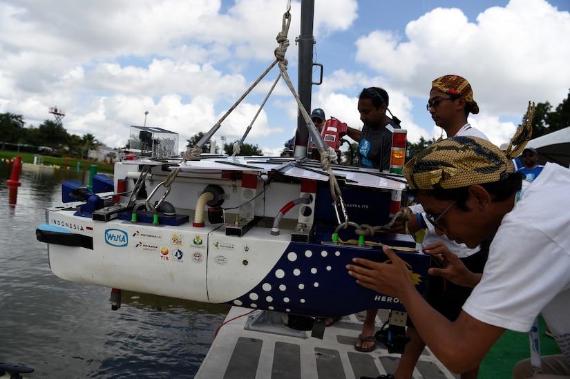 Students launch an autonomous boat during a competition.