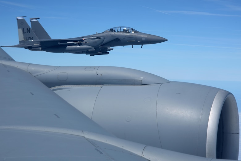 A U.S. Air Force F-15E Strike Eagle from the 492nd Fighter Squadron assigned to RAF Lakenheath flies alongside a U.S. Air Force KC-135 Stratotanker from over England, June 26, 2018. The honorary commanders were able to witnessed air refueling between the Bloody Hundredth and RAF Lakenheath. (U.S. Air Force photo by Airman 1st Class Benjamin Cooper)