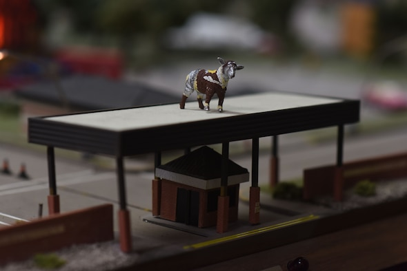 A miniature of Lt. Col. Ewe-Little, the sheep statue outside of Goodfellow Air Force Base's gates, stands watch over the Norma Brown Air Force Base model in the Louis F. Garland Department of Defense Fire Academy on Goodfellow Air Force Base, Texas, June 21, 2018. The sheep are a tie to the early history of San Angelo as the wool and sheep capital of the world. (U.S. Air Force photo by Airman 1st Class Seraiah Hines/Released)