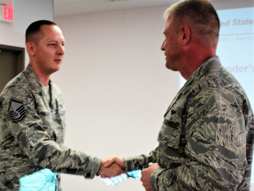 Master Sgt. Jason Wagner is coined by 340th FTG Commander, Col. Allen Duckworth during the 433rd TRS' June unit training assembly for exceptional performance. (Courtesy Air Force photo)
