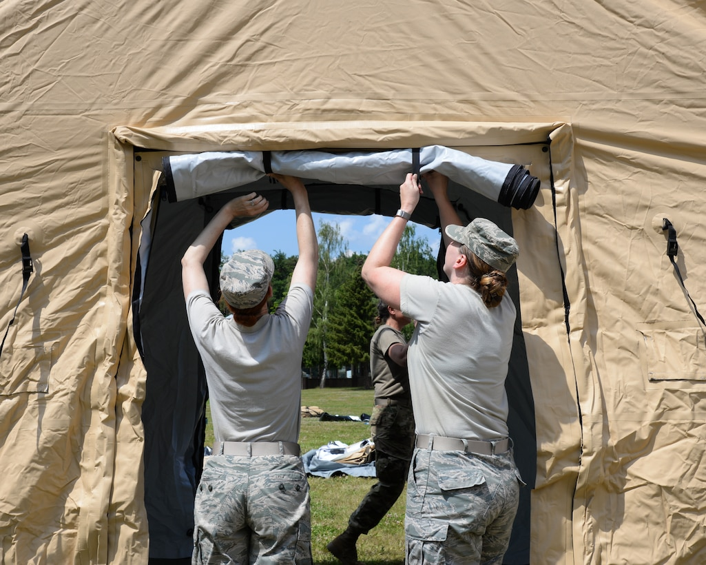 Airmen from the 86th Medical Group and the 86th Logistics Squadron set up an Expeditionary Medical Support System modular field hospital during en route patient staging training during Exercise Maroon Surge on Ramstein Air Base, Germany, June 4, 2018. The primary EMEDS missions are to: provide forward stabilization and resuscitative care; deliver primary care, dental services, and force health protection; and prepare casualties to evacuate to the next level of care. (U.S. Air Force photo by Airman 1st Class Ariel Leighty)