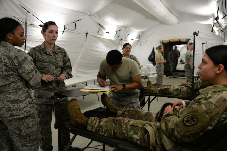 Airmen from the 86th Medical Group treat a patient with simulated minor injuries in an Expeditionary Medical Support System modular field hospital during en route patient staging training during Exercise Maroon Surge on Ramstein Air Base, Germany, June 9, 2018. Treatment at an EMEDS is a vital step in the en route care continuum, getting patients prepped for aeromedical evacuation to higher level of care. (U.S. Air Force photo by Airman 1st Class Ariel Leighty)