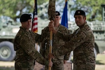 Lt. Col. Frank Biancardi, outgoing 11th Air Support Operations Squadron (ASOS) commander, passes the guidon to Col. Aaron Ullman, left, 3rd Air Support Operations Group commander during a squadron inactivation ceremony, June 21, 2018, at Fort Hood, Texas. As a part of the 93d Air Ground Operations Wing from Moody Air Force Base, Ga., the 11th ASOS 'Steel Eagles' mission will remain unchanged as they continue to support Ft. Hood and absorb into the 9th ASOS. The enhanced 9th ASOS will continue to provide tactical air support to align with any U.S. Army unit that needs air support for their scheme of maneuver. (U.S. Air Force photo by Senior Airman Daniel Snider)