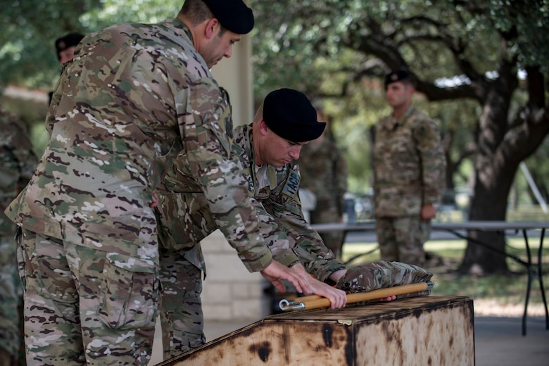 Lt. Col. Frank Biancardi, outgoing 11th Air Support Operations Squadron (ASOS) commander, and Master Sgt. Daniel Nestor, 11th ASOS superintendent, place an unassembled guidon to rest during a squadron inactivation ceremony, June 21, 2018, at Fort Hood, Texas. As a part of the 93d Air Ground Operations Wing from Moody Air Force Base, Ga., the 11th ASOS 'Steel Eagles' mission will remain unchanged as they continue to support Ft. Hood and absorb into the 9th ASOS. The enhanced 9th ASOS will continue to provide tactical air support to align with any U.S. Army unit that needs air support for their scheme of maneuver. (U.S. Air Force photo by Senior Airman Daniel Snider)