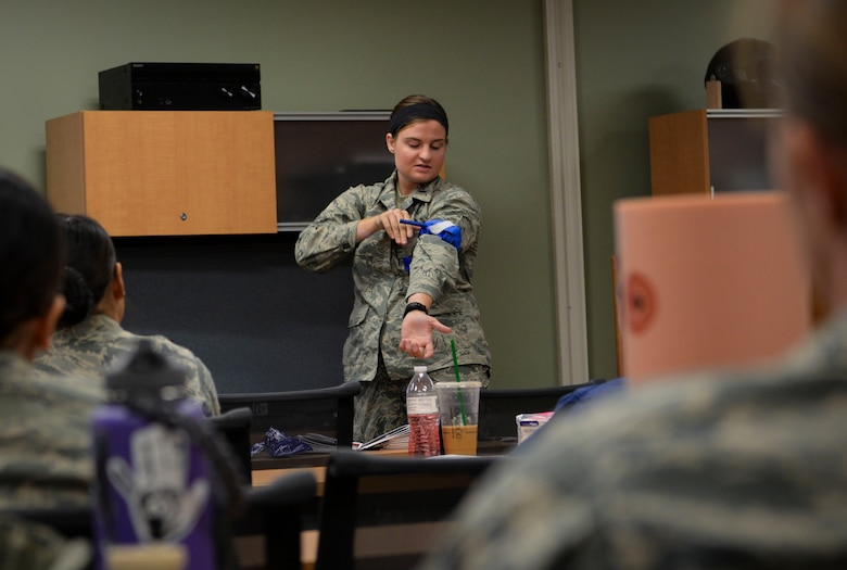 1st Lt. Caitlin Totman, 99th Inpatient Operations Squadron registered nurse, demonstrates how to properly use a tourniquet at Mike O'Callaghan Military Medical Center on Nellis Air Force Base, Nevada, June 22, 2018. The course stresses the mechanisms of the body and how bleeding can be drastically decreased by focusing on the three main methods of hemorrhage control: compression, tourniquet use and wound packing. (U.S. Air Force Photo by Airman Bailee A. Darbasie)