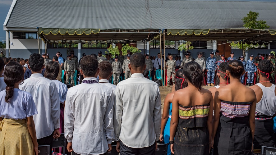 Timor-Leste students stand for the playing of their country's national anthem during the closing ceremonies for Pacific Angel (PAC ANGEL) 2018 at the Negri Saran Kote Secondary School in Suai, Cova Lima Municipality, Southwest Timor-Leste, June 18, 2018.