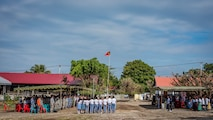 Attendees stand for the playing of the Timor-Leste national anthem during the closing ceremonies of Pacific Angel (PAC ANGEL) 2018 at the Negri Saran Kote Secondary School in Suai, Cova Lima Municipality, Southwest Timor-Leste, June 18, 2018.