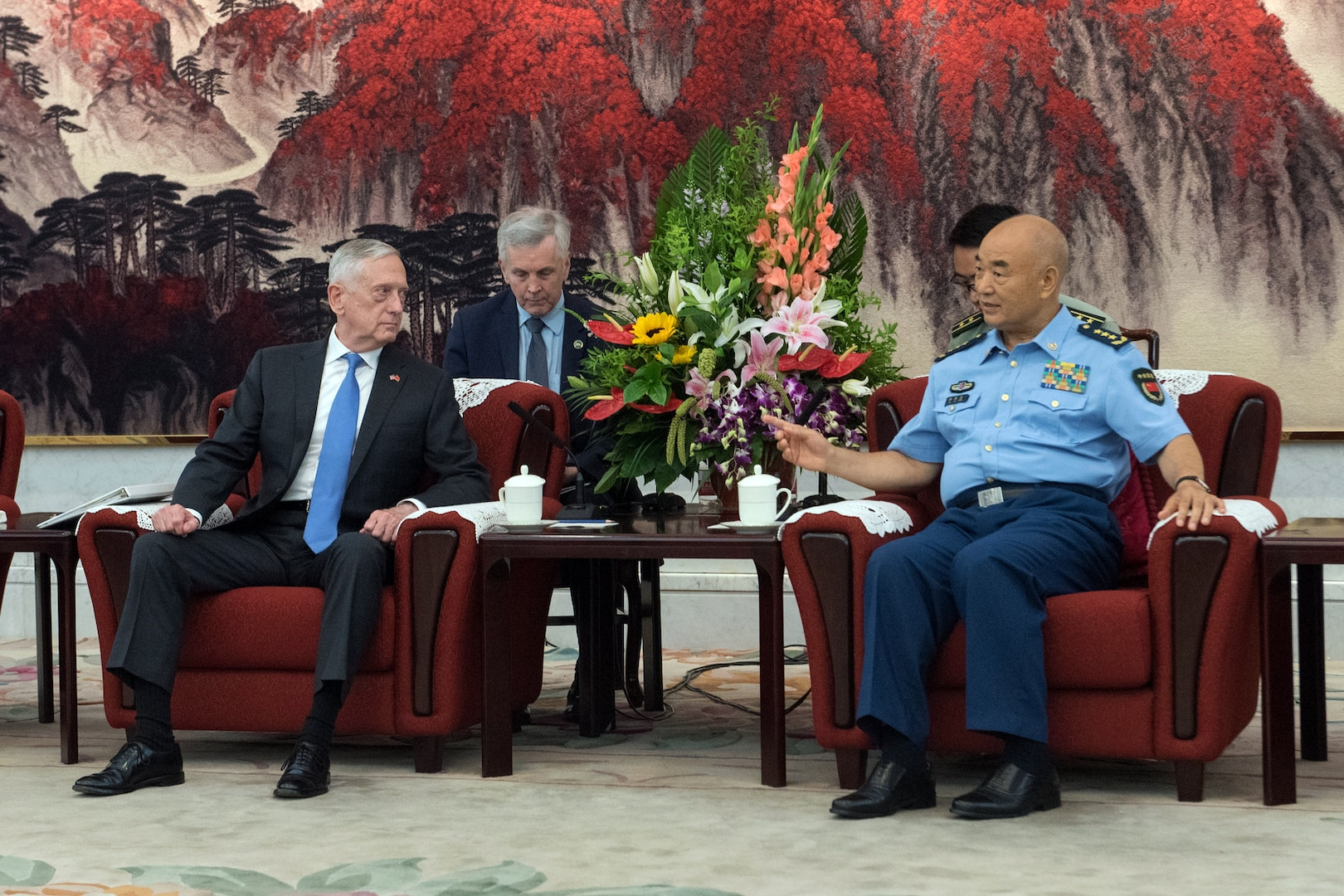 Defense Secretary James N. Mattis and a Chinese military officer sit in chairs and talk.