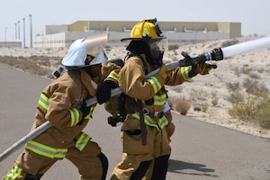 Senior Airman Rachel Johnson, 380th Civil Engineering Squadron emergency manager, and Staff Sgt. Staff Sgt. Jamie Perkins, 380th ECES firefighter, spray an open area with a fire hose during a 'Firefighter for a Day' training at Al Dhafra Air Base, June 25. This exercise demonstrated to Johnson, the 'Firefighter for a Day' the force that comes from a high pressure water hose and the strength needed to properly hold it. (U.S. Air Force photo by Staff Sgt. Erica Rodriguez)