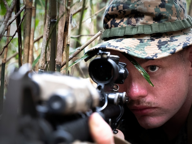 A Marine with Headquarters Company, Headquarters Battalion, 3rd Marine Division, sights in while posting 360 degree security during a patrol at the Jungle Warfare Training Center, Camp Gonsalves, Okinawa, Japan June 28, 2018. The Marines are participating in a one week course to improve their jungle survival skills.