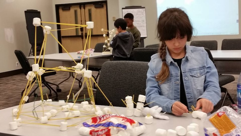 Felicity Maynor building her spaghetti and marshmallow tower