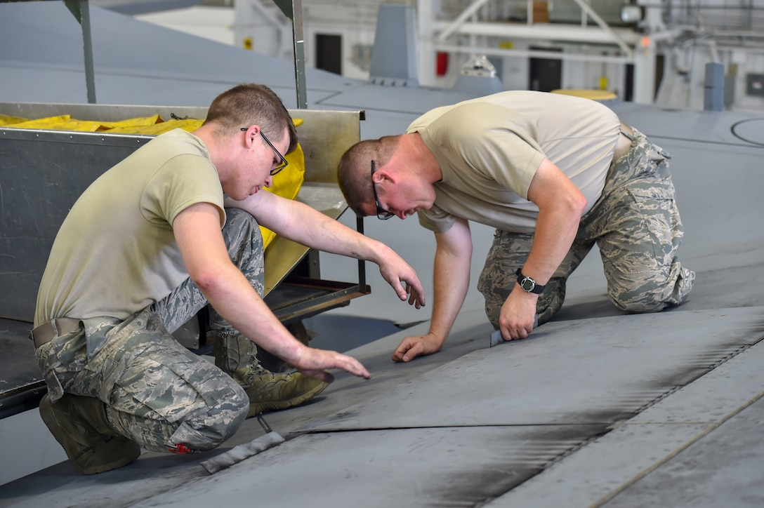 Airman Dustin Bruce and Master Sgt. Dan Scott, both aircraft maintenance technicians with the 910th Aircraft Maintenance Squadron, close a life raft compartment on the wing of a C-130H Hercules aircraft after removing the rafts here, June 13, 2018.